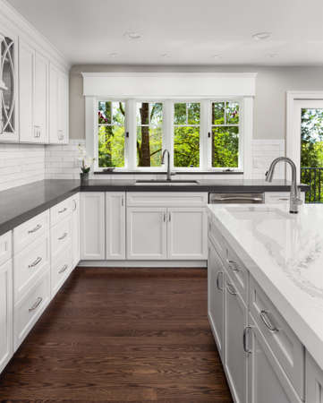 Beautiful New Kitchen in Luxury Home with Island, Hardwood Floors, Two Sinks, and View of Lush Foliage Banque d'images