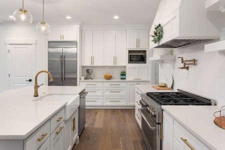 Belle cuisine avec évier de ferme et appareils électroménagers en acier inoxydable dans une nouvelle maison de luxe