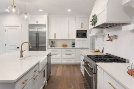 Hermosa cocina con fregadero de granja y electrodomésticos de acero inoxidable en nueva casa de lujo