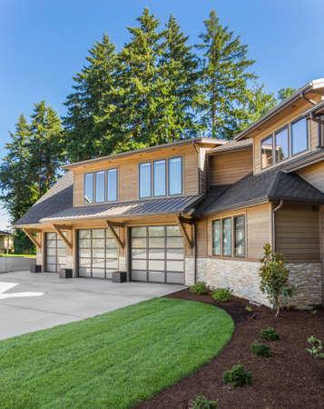 Luxe huis buitenkant op zonnige dag met blauwe lucht. Beschikt over een garage voor drie auto's, een grote oprit en een elegant ontwerp Stockfoto