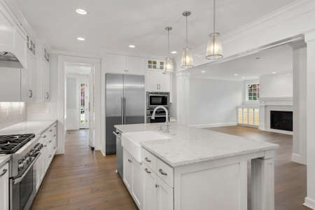 Bella cucina bianca in una nuova casa di lusso con pavimenti in legno ed elettrodomestici in acciaio inossidabile