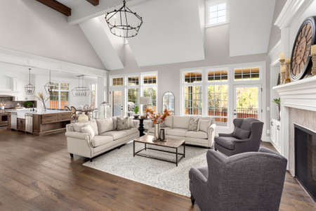 Beautiful living room and kitchen in new traditional style luxury home. Features vaulted ceilings,, and elegant furnishings.