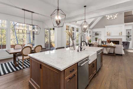 Schöne Küche in einem neuen Luxushaus im traditionellen Stil mit Quarz-Theken, Holzböden und Geräten aus Edelstahl Standard-Bild