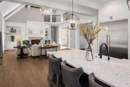 Bella cucina e soggiorno in una nuova casa di lusso in stile tradizionale. Presenta soffitti a volta, caminetto con fuoco scoppiettante e arredi eleganti.