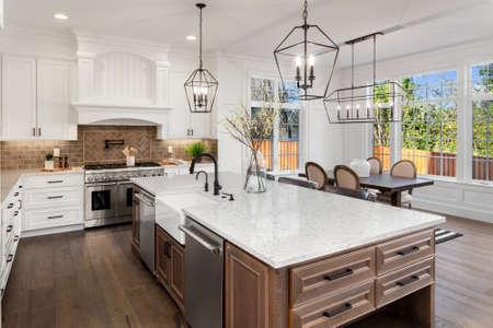Piękna kuchnia w nowym luksusowym domu w tradycyjnym stylu, z blatami kwarcowymi, drewnianymi podłogami i urządzeniami ze stali nierdzewnej