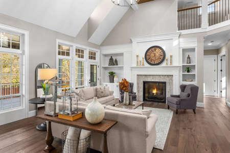 Bellissimo soggiorno in una nuova casa di lusso in stile tradizionale. Presenta soffitti a volta, caminetto con fuoco scoppiettante e arredi eleganti.