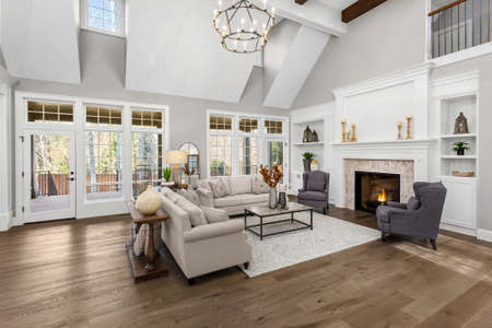 Beautiful living room in new traditional style luxury home. Features vaulted ceilings, fireplace with roaring fire, and elegant furnishings. Stockfoto
