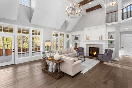 Hermosa sala de estar en nueva casa de lujo de estilo tradicional. Cuenta con techos abovedados, chimenea con fuego crepitante y muebles elegantes. Foto de archivo