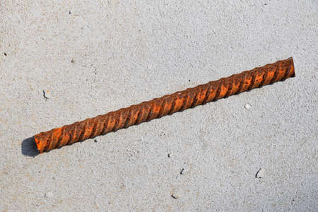 irresponsible: Cut piece of corroded stained rusty metal armature fitting on bubbled concrete floor