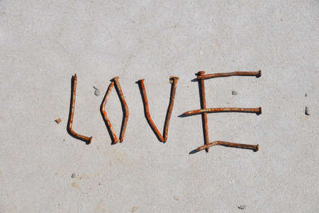 midlife: LOVE word formed by rusty nails at grey concrete background
