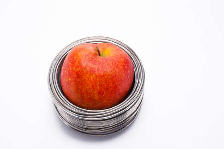wired: Wired apple: whole red apple in coils of aluminum wire isolated on white background