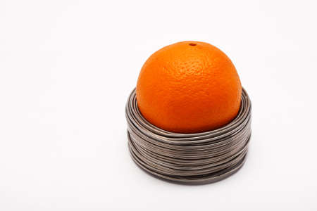 wired: Wired orange: whole orange in coils of aluminium wire isolated on white background