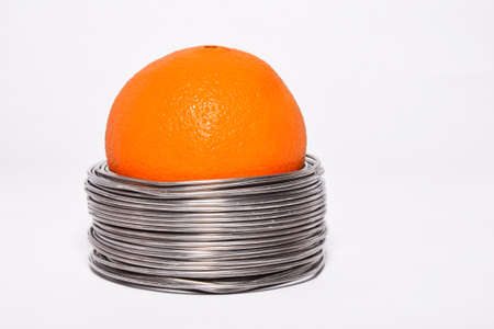 constrained: Wired orange: whole orange in coils of aluminium wire isolated on white background