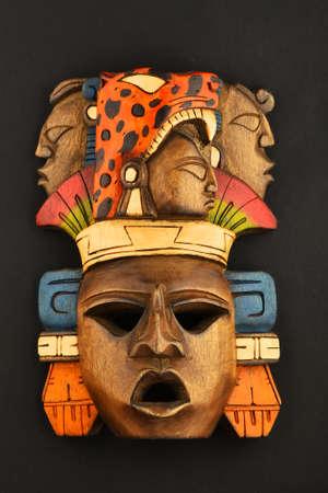 cultura maya: Máscara india maya azteca de madera tallada pintada con rugiente jaguar y rostros humanos aislados en el fondo de papel negro