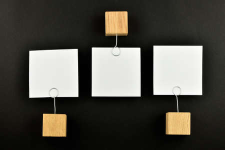 holders: Opposite Opinion - three white paper notes with wooden holders in different directions isolated on black paper background for presentation