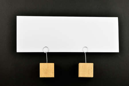holders: Together, One big white paper note with two wooden holders isolated on black paper background for presentation Stock Photo