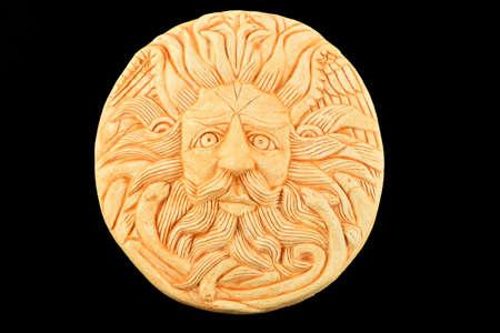 minerva: Tourist ceramic souvenir replica of male Gorgon Medusa head in Minerva temple in Roman Bath in England isolated on black
