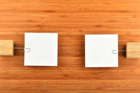 opinions: Opposite Opinions - Two white paper notes with wooden holders in different directions on bamboo wooden background for presentation Stock Photo