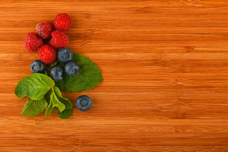 Taste of summer - cutting board with mellow blueberries, raspberries and mint leaves – add your text Фото со стока