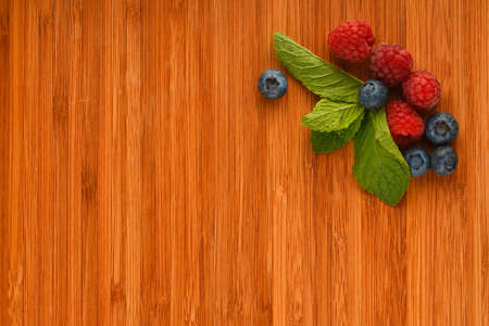 mellow: Taste of summer - cutting board with mellow blueberries, raspberries and mint leaves – add your text