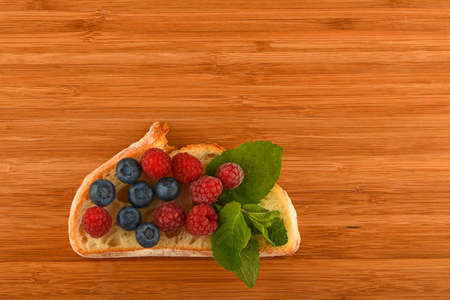 mellow: Better than caviar - cutting board with sandwich of mellow blueberries, raspberries and mint leaves on slice of wheat bread