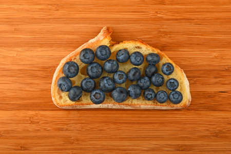 mellow: Wooden bamboo cutting board with sandwich of mellow blueberries on slice of wheat bread