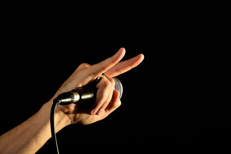 pop idol: Male hand holding microphone with devil horns rock metal sign isolated on black background Stock Photo