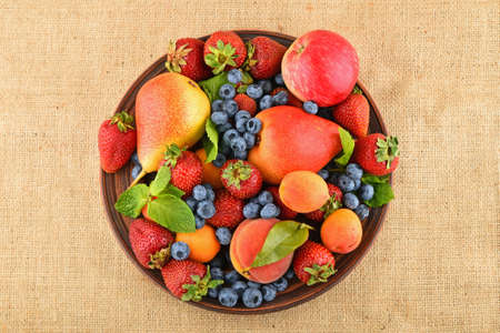 mellow: Mellow fresh summer fruits and berries mix with mint leaves in ceramic plate on burlap jute canvas, strawberries, blueberries, apricots, peach, apple and pear