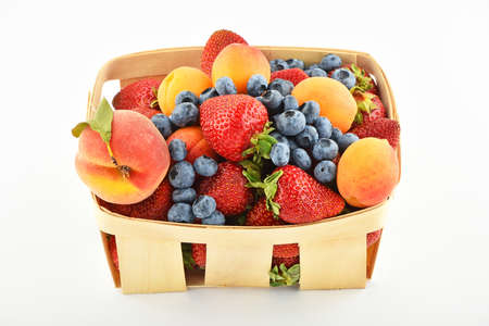mellow: Mellow fresh summer strawberries, blueberries, apricots and peach in wooden basket isolated on white background