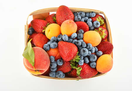 mellow: Mellow fresh summer strawberries, blueberries, apricots and peach in wooden basket isolated on white background, top view Stock Photo