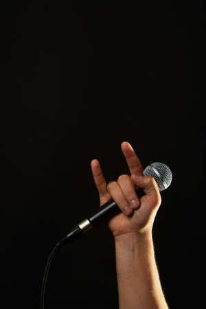cuernos: Mano masculina que sostiene el micrófono con cuernos de diablo signo rock metal aislado en el fondo negro