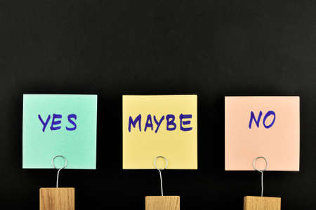 maybe: Yes, no, maybe, three paper notes, green, yellow, pink, with wooden holder isolated on black paper background for presentation