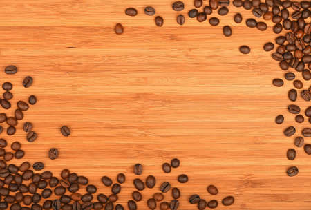 distributed: Roasted Arabica coffee espresso beans shape corners border over wooden bamboo board background Stock Photo