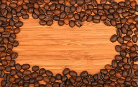 distributed: Roasted Arabica coffee espresso beans shape solid border frame over wooden bamboo board background Stock Photo