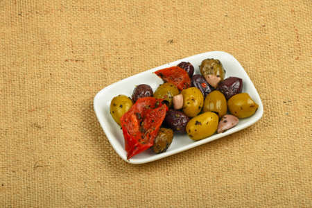 piped: White plate of Mediterranean snack of red and green olives and pickled red pepper on burlap jute canvas
