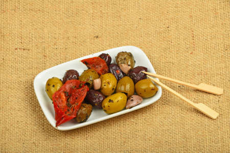 piped: White plate of Mediterranean snack of red and green olives and pickled red pepper with skewers on burlap jute canvas Stock Photo