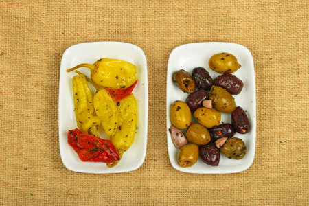 piped: Mediterranean snack of red and green olives and pickled green pepper in two white plates on burlap jute canvas