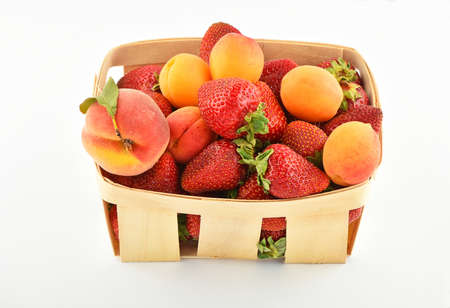 mellow: Mellow fresh summer strawberries, apricots and peach in wooden basket isolated on white background