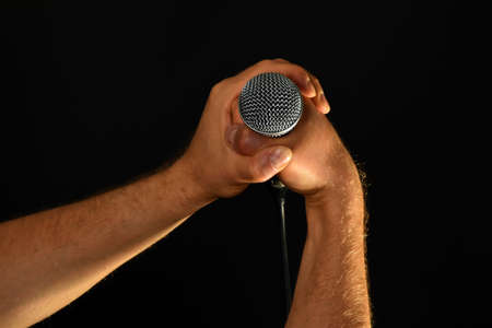 pop idol: Two male hands holding microphone with wire cable isolated on black background