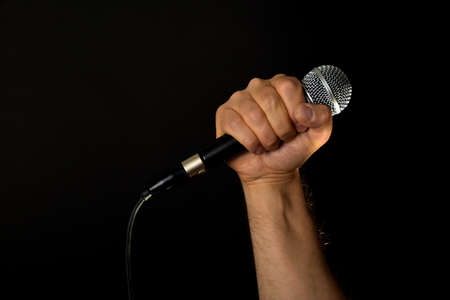 Male hand holding microphone with wire cable isolated on black background Stock Photo