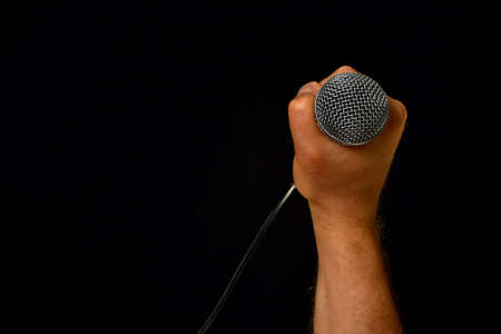 pop idol: Male hand holding microphone with wire cable isolated on black background Stock Photo