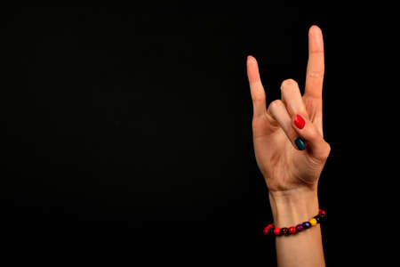 female devil: Female hand with devil horns rock metal sign symbol gesture and colorful wooden beads isolated on black background