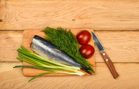 table surface: Herring double fillet with onion, dill and tomatoes on bamboo board win small knife on vintage wooden table surface