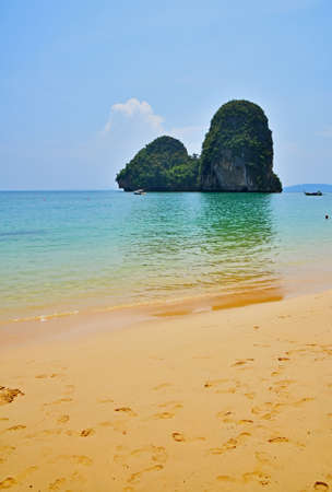 green footprint: Paradise tropical sunny sand sea beach with sky blue water and forest rock
