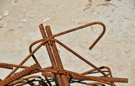 armature: Rusty corroded stained metal pieces of wire, fitting, armature on a dirty concrete floor