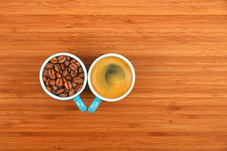 selected: Two blue coffee cups of espresso and roasted Arabica beans over wooden bamboo board background