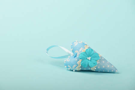 teaser: One small textile heart with mulberry paper flower and ribbon on tender blue background Stock Photo