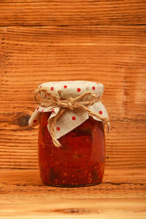 salad decoration: One glass jar of homemade pickled pepper, paprika and eggplant salad with dotted textile top decoration at brown vintage wooden surface