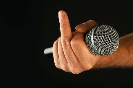 fuck: Male hand holding microphone with finger fuck off insult ignore gesture on black background