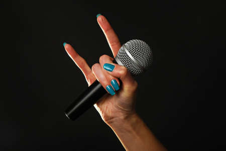 Woman hand with blue nails holding microphone with devil horns rock metal sign isolated on black background Standard-Bild